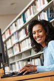 Metà di donna di età che lavora al computer in biblioteca Fotografie Stock