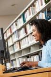 Metà di donna di età che lavora al computer in biblioteca Fotografia Stock