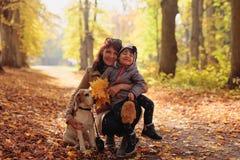 Metà di donna di età con la bambina ed il cane da lepre nel parco di autunno fotografia stock libera da diritti