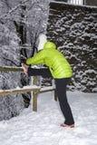Metà di donna invecchiata che fa allungamento nel parco della città di inverno Fotografie Stock