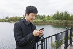 Metà di invio di messaggi di testo adulto felice dell'uomo d'affari tramite il telefono cellulare all'inferriata del ponte immagine stock libera da diritti