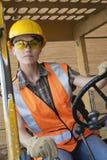 Metà di lavoratore dell'industria della femmina adulta che conduce carrello elevatore a forcale fotografia stock libera da diritti