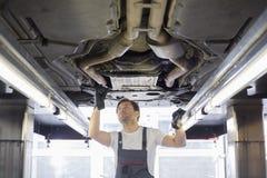 Metà di lavoratore di riparazione del maschio adulto che ripara automobile in officina Immagini Stock