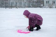 Metà di ragazza di età sotto il cappuccio che gioca con la neve Immagine Stock