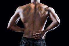 Metà di sezione dell'atleta muscolare che soffre con il dolore alla schiena Fotografie Stock