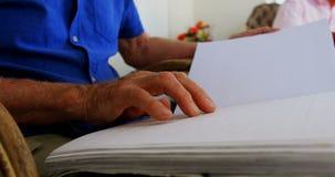 Metà di sezione dell'uomo senior cieco che legge un libro di Braille alla casa di cura 4k archivi video