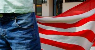 Metà di sezione della bandiera americana caucasica della tenuta dello scolaro a scuola 4k video d archivio