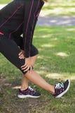 Metà di sezione della donna che allunga la sua gamba durante l'esercizio al parco Immagini Stock Libere da Diritti