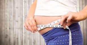 Metà di sezione della donna incinta con nastro adesivo di misurazione contro il pannello di legno confuso Fotografie Stock
