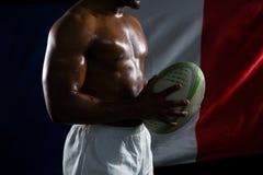 Metà di sezione della palla di rugby senza camicia della tenuta dello sportivo contro la bandiera italiana immagini stock libere da diritti