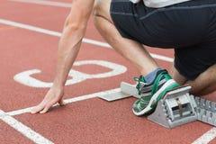 Metà di sezione di un uomo pronto a correre sulla pista corrente Immagini Stock Libere da Diritti