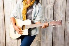 Metà di sezione di una donna casuale sorridente che gioca chitarra Immagine Stock