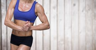 Metà di sezioni della donna muscolare contro il pannello di legno confuso Fotografie Stock Libere da Diritti