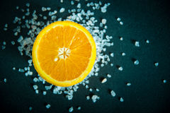 Metà di un'arancia con i cristalli rosa himalayani del sale su fondo scuro Fotografia Stock Libera da Diritti