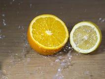 Metà di un'arancia e un limone e gocce di acqua Fotografia Stock
