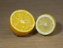 Metà di un'arancia e un limone e uno spruzzo Fotografie Stock