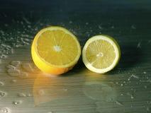 Metà di un'arancia ed il limone e le gocce Fotografia Stock