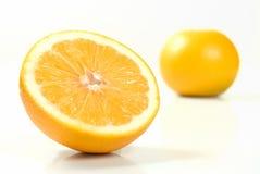Metà di un mandarino con l'intero mandarino isolato fotografie stock