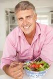 Metà di uomo di età che gode dell'insalata Fotografie Stock Libere da Diritti