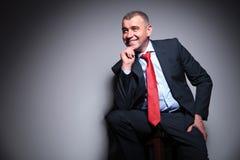 Metà di uomo invecchiato sorridente di affari che si siede su un panchetto Fotografie Stock
