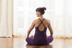 Metà di yoga di pratica invecchiata della donna caucasica Sedendosi nel vestito porpora del corpo nella posa di rilassamento cont fotografia stock libera da diritti