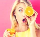Metà felici delle arance della tenuta della giovane donna Fotografia Stock