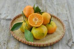 Metà tagliata arancio fresca in canestro di vimini su fondo di legno fotografia stock