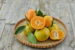 Metà tagliata arancio fresca in canestro di vimini su fondo di legno fotografie stock libere da diritti