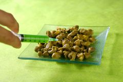 Metáfora de la investigación alimentaria con la jeringuilla verde Fotografía de archivo