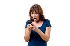 Met afschuw vervulde vrouw die op middelbare leeftijd mobiel haar bekijken royalty-vrije stock foto