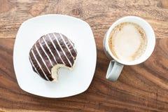 Met chocolade bedekte geleidoughnut op houten lijst royalty-vrije stock foto's