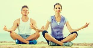 Met de benen over elkaar de yoga van de paarpraktijk op strand in ochtend Stock Afbeeldingen
