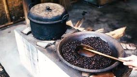 Met de hand bewegend ongekookte koffiebonen in pan op oude traditionele manier stock footage