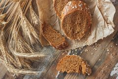 Met de hand gemaakt brood met zemelen en oren van tarwe, houten achtergrond stock afbeeldingen