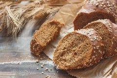 Met de hand gemaakt brood met zemelen en oren van tarwe, houten achtergrond stock foto