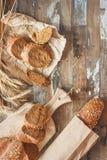 Met de hand gemaakt brood met zemelen en oren van tarwe, houten achtergrond stock fotografie