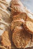 Met de hand gemaakt brood met zemelen en oren van tarwe, houten achtergrond stock afbeelding