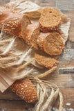 Met de hand gemaakt brood met zemelen en oren van tarwe, houten achtergrond stock foto's