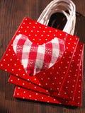 Met de hand gemaakt katoenen zacht hart op een stapel van huidige zakken Stock Foto's