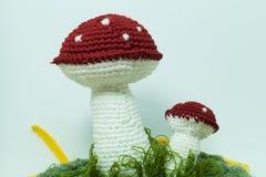 Met de hand gemaakt kniited stuk speelgoed paddestoel op wit Stock Foto's