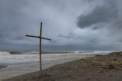 Met de hand gemaakt kruis van staven op een stormachtig strand Stock Afbeeldingen