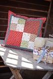 Met de hand gemaakt lapwerkkussen met het naaien van hulpmiddelen op houten lijst Stock Foto