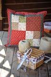 Met de hand gemaakt lapwerkkussen met het naaien van hulpmiddelen op houten lijst Royalty-vrije Stock Afbeelding