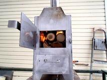 Met de hand gemaakt roestvrij staal houten fornuis met open as binnen kuil en ovendeur, brandend brandhout royalty-vrije stock afbeeldingen