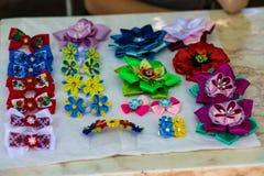 Met de hand gemaakte bloemendiehaarspelden van rode roze bloemen worden gemaakt Modieuze hand - gemaakte haarspelden van bloemen  Stock Foto