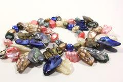 Met de hand gemaakte die halsband van kleurrijke moeder van parel op een witte achtergrond wordt gemaakt stock afbeelding
