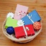 Met de hand gemaakte die zepen op een mand met bloemen wordt verfraaid Stock Foto