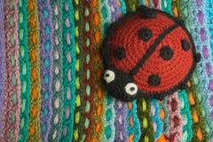 Met de hand gemaakte gebreide lieveheersbeestjestuk speelgoed kleurrijke achtergrond Stock Afbeelding