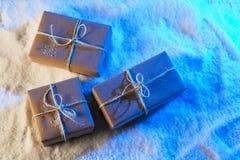 Met de hand gemaakte giftvakjes van ambachtdocument over sneeuw houten lijst in blauw licht Royalty-vrije Stock Foto