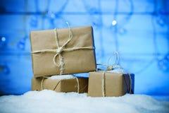 Met de hand gemaakte giftvakjes van ambachtdocument over sneeuw houten lijst in blauw licht Stock Afbeelding
